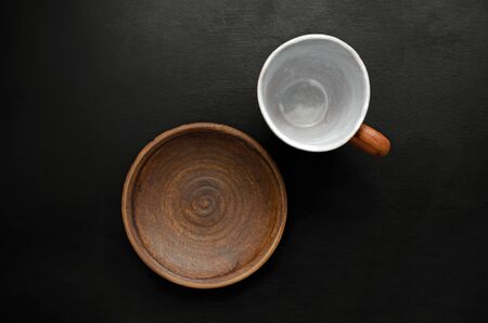 Empty brown ceramic tableware cup and plate on a black slate background. The concept of food and its absence. copy space Banque d'images