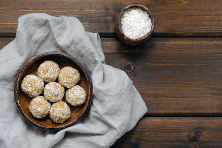 nutrition for athletes healthy snack. homemade healthy energy balls made from natural ingredients of dried oatmeal honey dried fruit nuts in coconut flakes without sugar on a ceramic plate ingredients Banque d'images