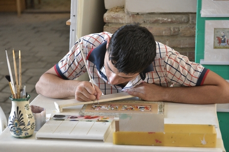 accurately: Bukhara, Uzbekistan - August 5, 2015: School of Oriental arts. A young painter working on his new painting.