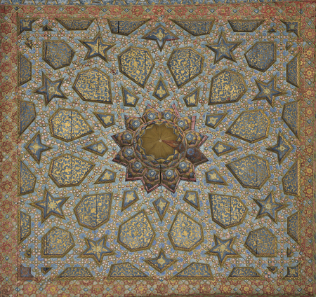 Vintage oriental patterns decorate the ceiling in Bukhara. Фото со стока