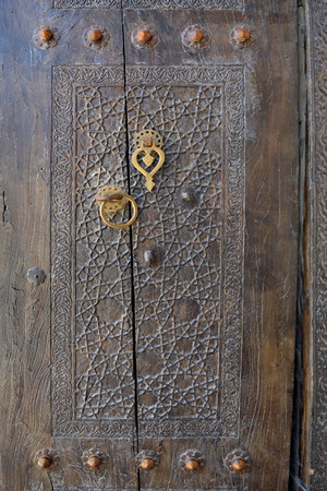 The old wooden door, decorated with Oriental ornaments and handles handmade from bronze.