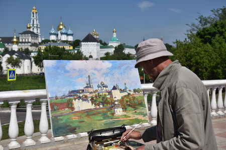 Sergiev Posad, Russia - may 28, 2016: a Street painter draws a picture of the Cathedral of the Holy Trinity-St. Sergius Lavra. Sergiyev Posad is included into the Golden ring of Russia and is a pilgrimage center of the Christian world. Фото со стока - 62936046