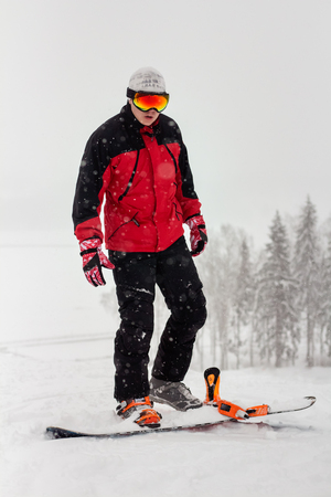 young man snowboarding in snowy weather