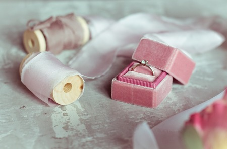 romantic present: pink velvet box with a wedding ring and light satin ribbons on a gray background Banco de Imagens