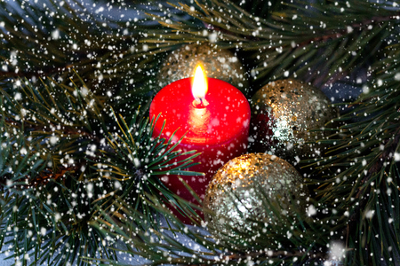 Red burning candle and golden Christmas balls with a fir branch under going snow