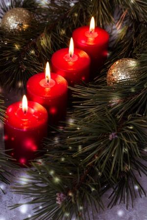 Vier rot beleuchtete Adventskerzen umgeben von grünen Tannenzweigen
