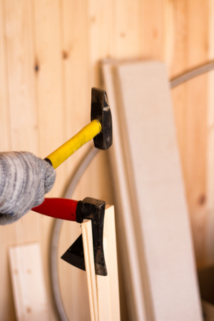 Building tools. Woodwork. Hammer and ax in male hands