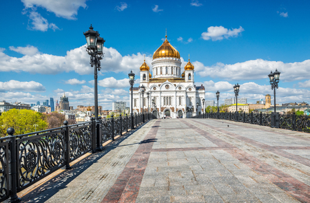 The blue sky and white clouds above the Cathedral of Christ the Savior. View from the Patriarchal bridge with openwork lanterns.