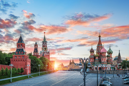 Spassky Tower and St. Basils Cathedral on Red Square in Moscow and the colorful sky with the sun