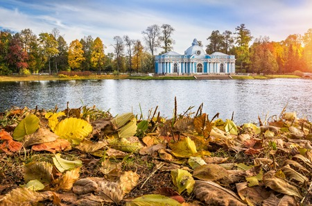 The building of the Blue Grotto in Tsarskoye Selo on the shore of the pond and fallen autumn leaves
