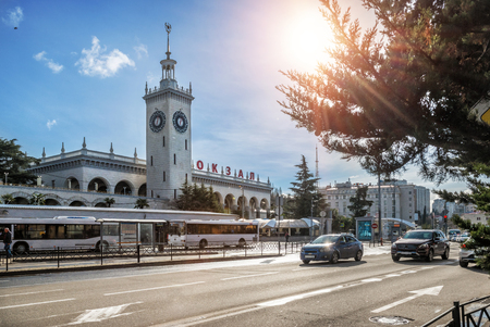 Railway station with a tower in Sochi under a blue sky in a sunny day. Inscription on the facade: Railway station.