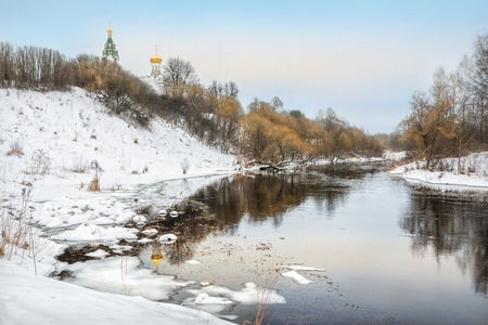 The river flows among the winter snow and the temple with the golden dome on the high bank Фото со стока