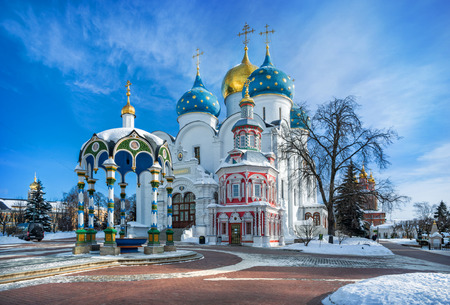 White stone Uspenskiy Cathedral, a well and a chapel in the Lavra in Sergiev Posad on a sunny winter day
