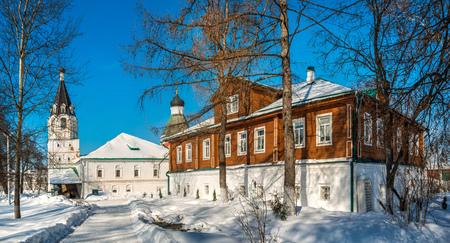 Pokrovskaya church and a wooden house in the Alexandrovskaya Sloboda on a sunny winter day Editorial