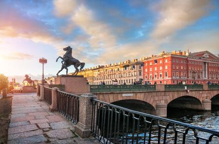 Sombres sculptures de chevaux sur le pont Anichkov à Saint-Pétersbourg sur fond de ciel ensoleillé d'été au coucher du soleil Éditoriale