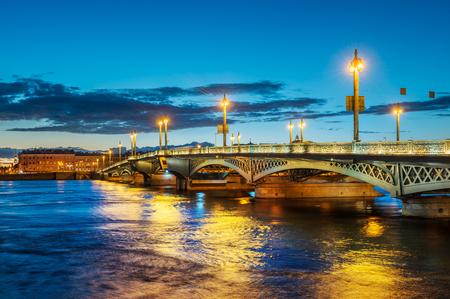 Le pont de l'Annonciation à Saint-Pétersbourg dans l'éclairage de nuit et la rivière Neva