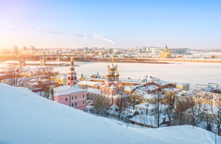 View of the Christmas Church and the Alexander Nevsky Cathedral along the banks of the Volga River in Nizhny Novgorod on a sunny winter evening Foto de archivo