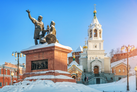 Monument to Minin and Pozharsky and the Bell Tower of the Church of the Nativity of St. John the Forerunner near the walls of the Nizhny Novgorod Kremlin in the light of the winter evening sun. Caption: a citizen of Minin and Prince Pozharsky. Grateful Russia Banco de Imagens