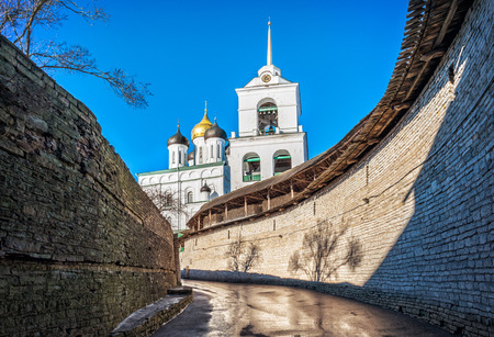 Zakhab (entrance corridor between the stone walls) in the Pskov Kremlin spring sunny day overlooking the Trinity Cathedral.