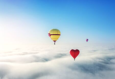Beautiful balloons in the blue sky over white clouds and the sun Stok Fotoğraf