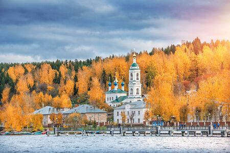 Barbarian Church on the shore among the red autumn trees in the city of Plyos. View from the water of the Volga.