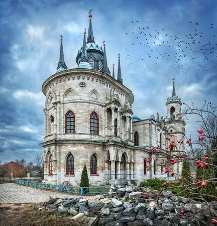 Vladimir Church in the village of Bykovo, Moscow Region and a bush with red berries on an autumn cloudy day and birds in the clouds