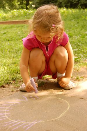 little girl drawing sun with chalk photo