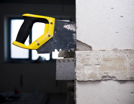 a hand saw in the wall at homerepair Stok Fotoğraf