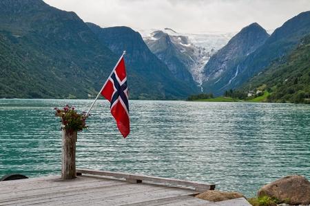 norway flag: The Norwegian flag against the Norwegian landscape Stock Photo