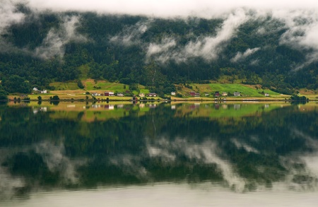 Foggy landscape with mirror reflexion in fjord water Stock Photo - 13291772