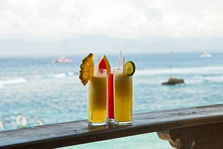 Three glasses with fresh juice against the sea Stock Photo - 13646742