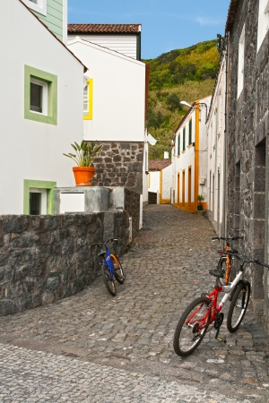 The narrow street of a small town with three bicycles 免版税图像