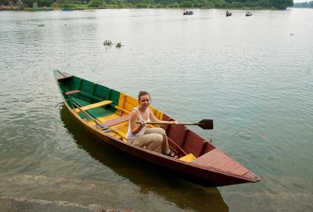 oar: A nice girl in a boat rowing one oar