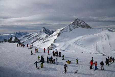 Mountain skiers and snowboarders prepare for descent from mountain