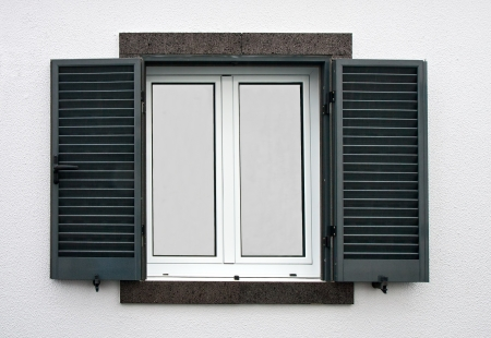 Window with open shutters on a white stone wall