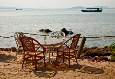 Table with wicker chairs on the  seacoast, beach vacation photo