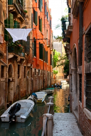 Boats moored in a narrow canal of Venice  photo