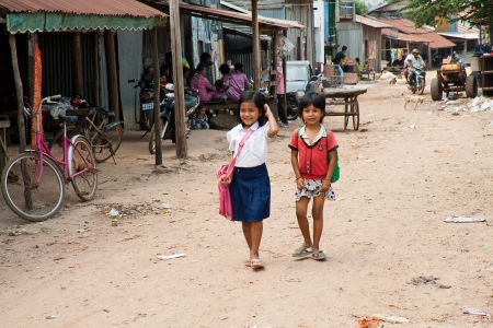 SUBURB SIHANOUKVILLE, CAMBODIA. FEBRUARY 26, 2013 - Two small Cambodian girls go home from school