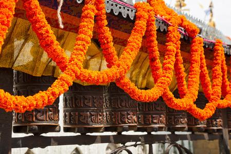 Swayambhunath  Prayer wheel, decorated with garlands of flowers Stock Photo - 27551886