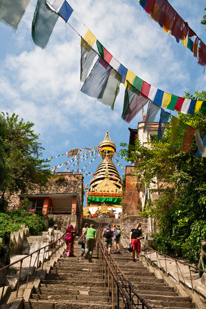 KATHMANDU, NEPAL - SEPTEMBER 30, 2012 - Tourists walk up the stairs to the stupa Swayambunath