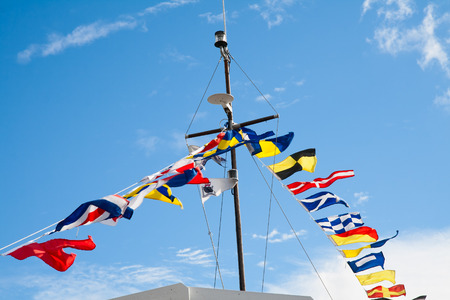 Mast with signal flags against blue sky
