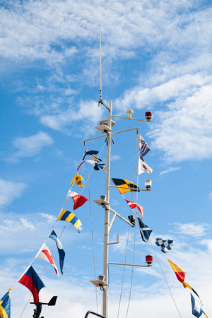 Mast with nautical signal flags against blue sky