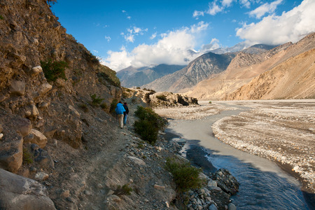 Trekking in the Himalayas  Two travelers go along the river Kali Gandaki photo