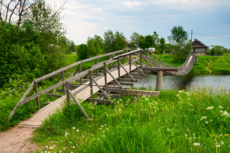 country house: Wooden suspension bridge across the river in a Russian village
