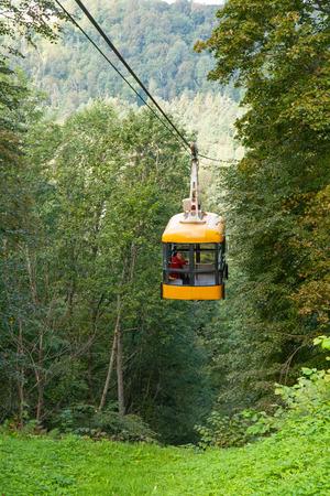 sigulda: Sigulda, Letonia - 02 de septiembre 2014 - Un anciano va en una cabina de telef�rico a trav�s del r�o Gauja