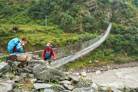 kali: TATOPANI, NEPAL - OCTOBER 04, 2012 - Girl tourist crossing the river Kali Gandaki on a suspension bridge, accompanied by Nepalese guide Editorial