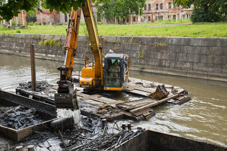 dredger: ST. PETERSBURG, RUSSIA - JULY 26, 2015: Working on the dredger clears the bottom of the canal from the scrap metal and sediment Editorial