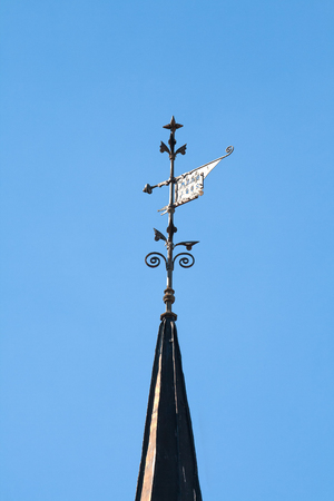 vane: Metal weather vane on a ancient building in Riga closeup
