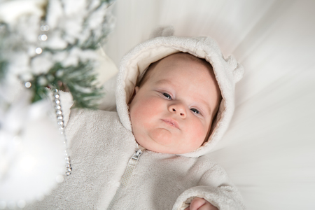baby near christmas tree: A baby in a white fur suit lies near the Christmas tree