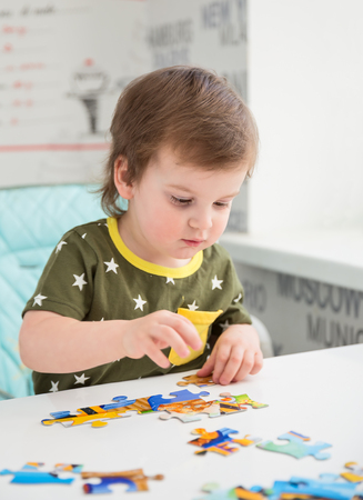 toddler boy: Little boy or toddler playing with a puzzle, child development concept Stock Photo